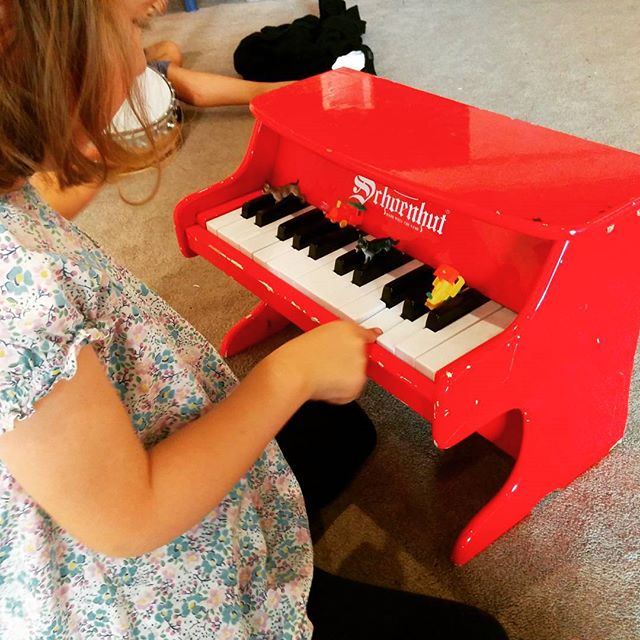 playing the cutest little red piano at music class
